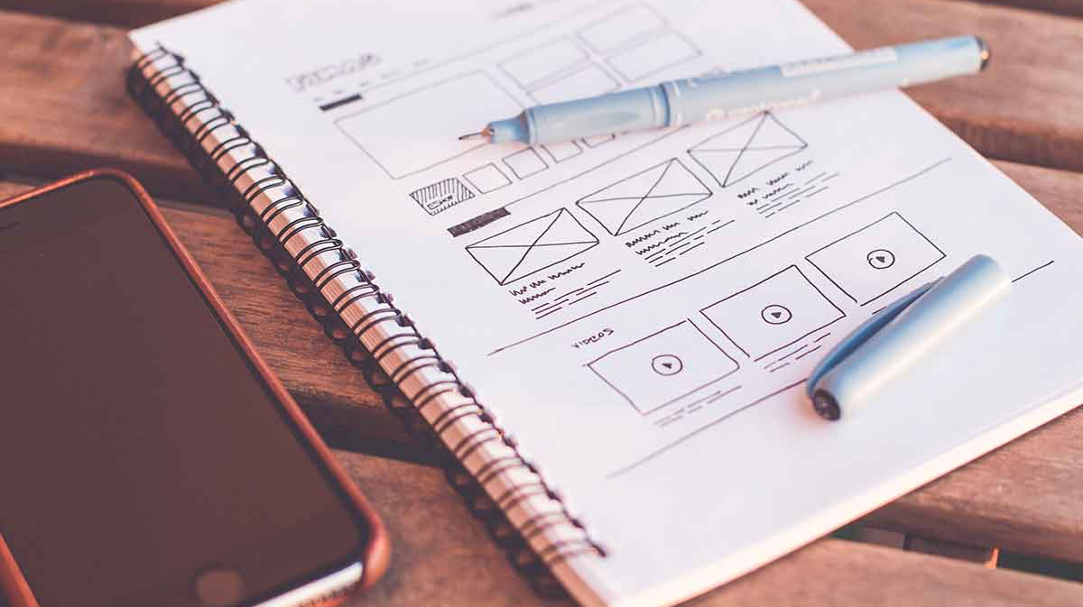 Notebook with a sketch of a website wireframe design